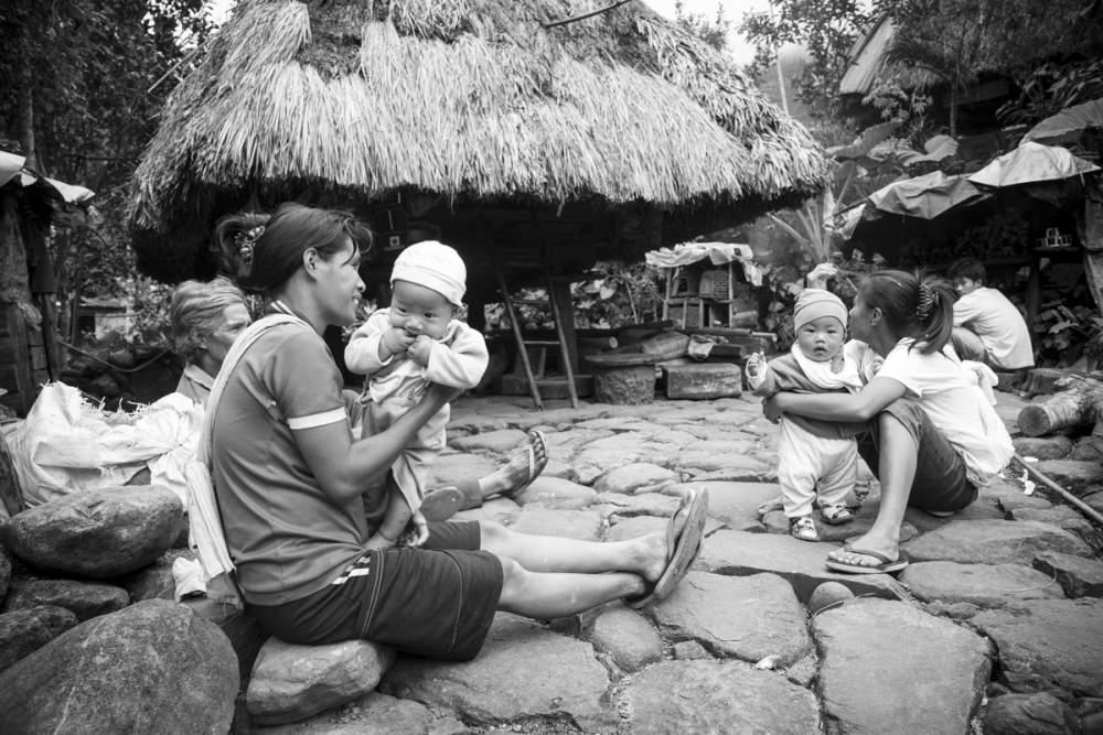 Fin de journée devant un habitat traditionnel Ifuago, Cambulo, île de Luzon